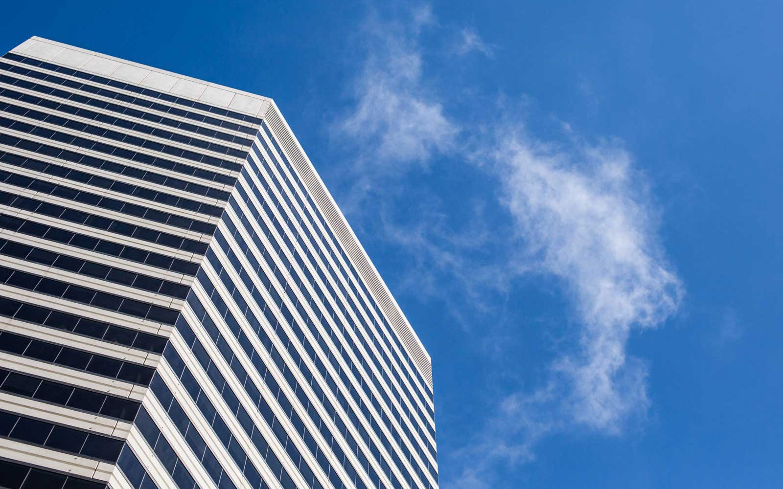 aaa_clean-skyscraper-view-from-below-against-blue-sky-and-clouds-picjumbo-com